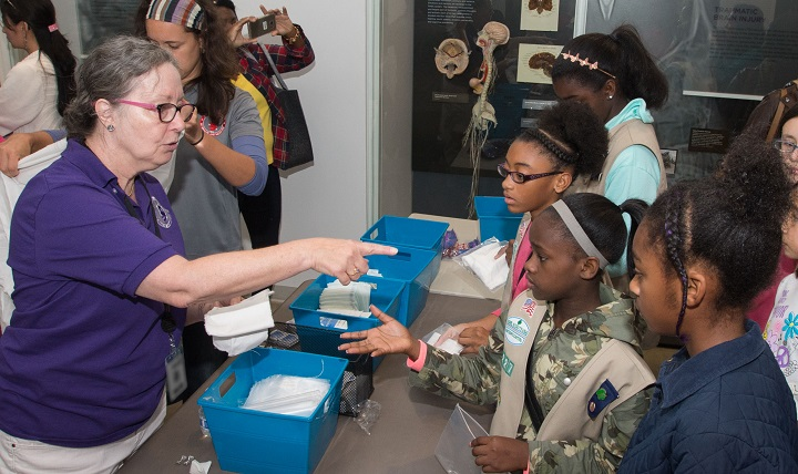 """Roseann Flyte, a volunteer at the National Museum of Health and Medicine, talks about the proper materials for a first aid kit during the NMHM's """"Scout Day"""" on Saturday, Oct. 15, 2016, in Silver Spring, Maryland. (National Museum of Health and Medicine photo by Matthew Breitbart)"""
